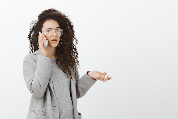 Portrait de petite amie interrogée frustrée aux cheveux bouclés en manteau gris et lunettes, levant la main sans aucune idée tout en parlant sur smartphone