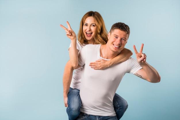 Portrait d'une petite amie souriante sur le dos de son petit ami, montrant le signe de la victoire
