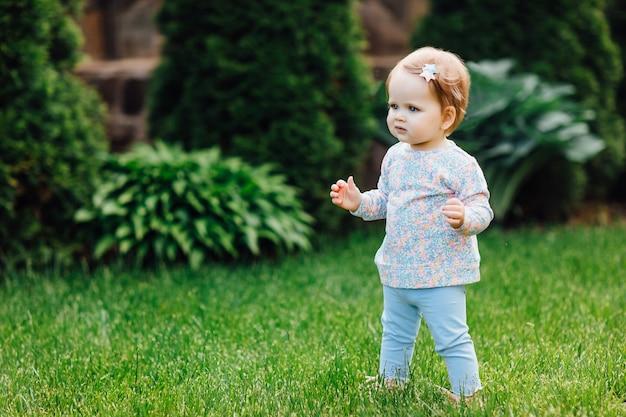 Portrait de petite belle fille, dans le beau parc verdoyant, sourit doucement