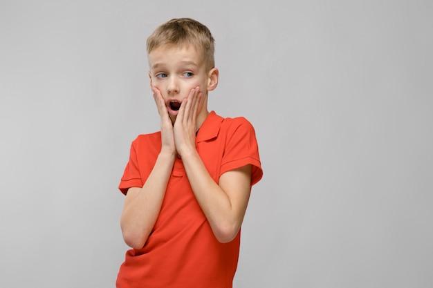 Portrait de petite blonde surprise étonné garçon caucasien en t-shirt orange avec la bouche ouverte sur fond gris