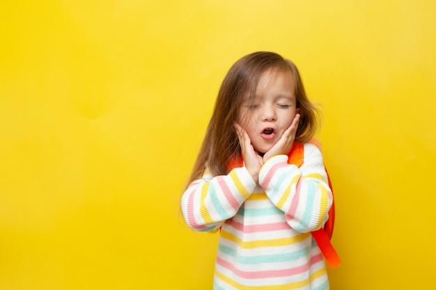 Portrait d'une petite écolière drôle avec sa bouche ouverte avec un sac à dos sur fond jaune