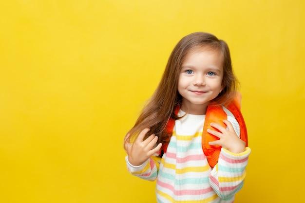 Portrait d'une petite écolière mignonne avec un sac à dos dans un cavalier sur un fond de couleur jaune