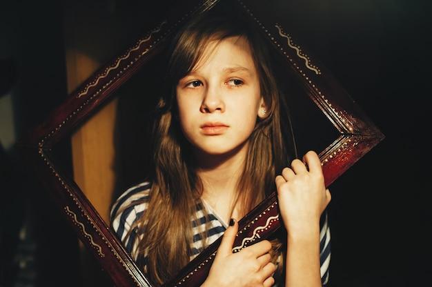Portrait de petite femme dans un cadre en bois