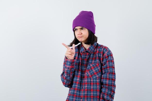 Portrait de petite femme pointant vers l'extérieur en chemise à carreaux et bonnet à la recherche d'hésitant