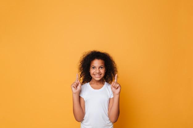 Portrait d'une petite fille africaine souriante, pointant les doigts
