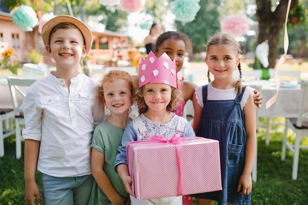Un portrait de petite fille avec des amis et présente à l'extérieur dans le jardin en été.