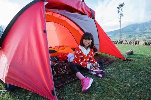 Portrait de petite fille appréciant le camping avec le beau paysage de colline