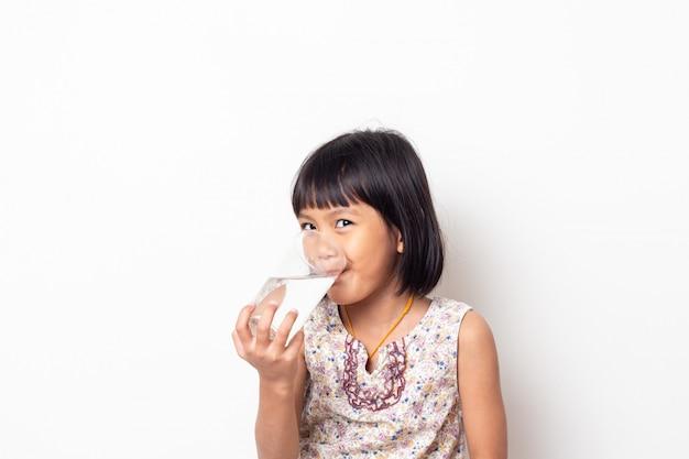 Portrait de petite fille asiatique eau potable sur fond noir blanc