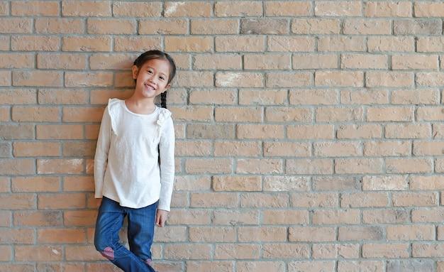 Portrait d'une petite fille asiatique heureuse avec des cheveux en queue de cochon en jeans et une chemise blanche debout au fond de mur de brique avec espace de copie.