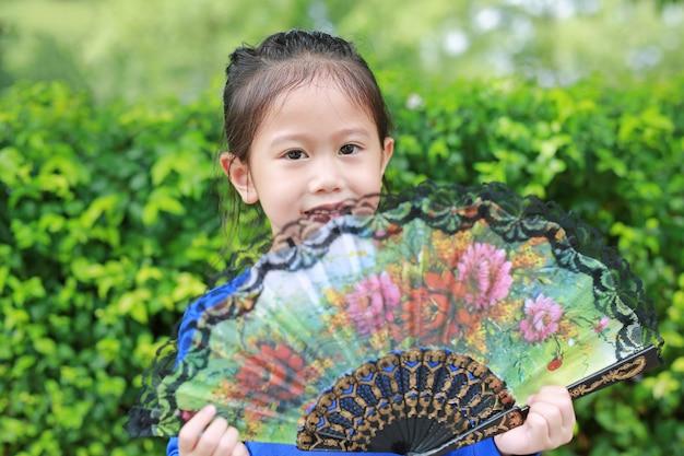 Portrait de petite fille asiatique avec holding ventilateur de style chinois dans le jardin d'été.