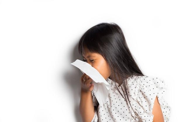 Portrait de petite fille asiatique malade d'essuyage et de nettoyage du nez avec des tissus