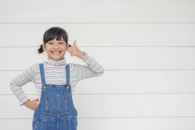 Portrait d'une petite fille asiatique mignonne avec son coup de poing, concept publicitaire, petite adolescente asiatique avec le fond blanc et l'espace