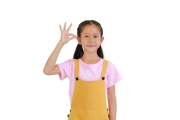 Portrait de petite fille asiatique souriante avec la main suspendue quelque chose de blanc isolé sur fond blanc.