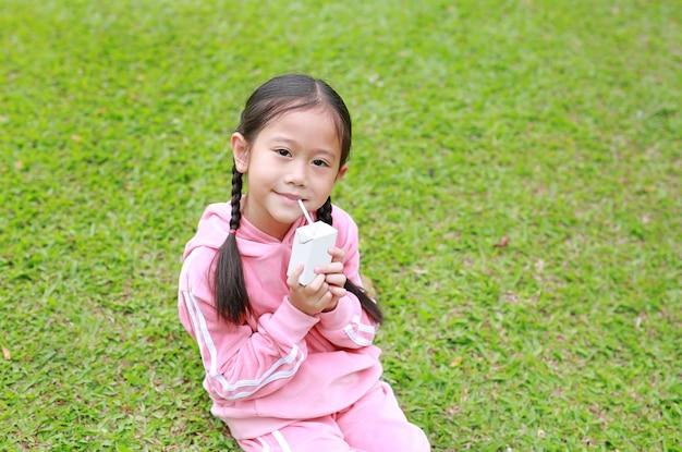 Portrait de petite fille asiatique en tissu sport, boire du lait