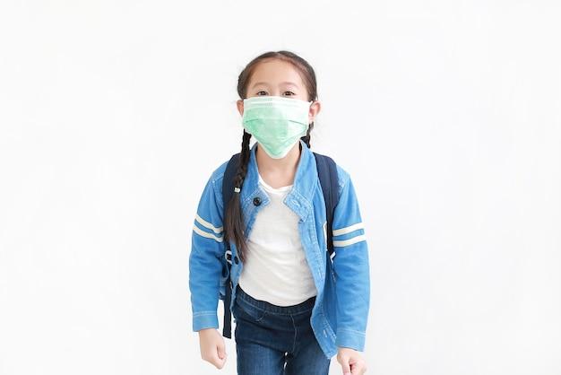 Portrait petite fille asiatique en uniforme scolaire décontracté portant un masque médical avec sac à dos isolé sur fond blanc. prise de vue en studio