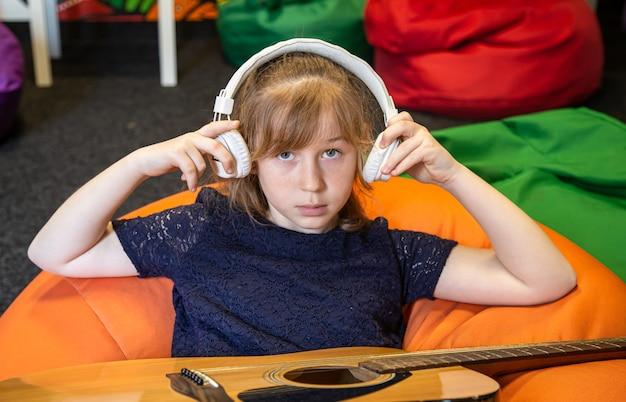 Portrait d'une petite fille au casque et avec une guitare en train d'apprendre la musique