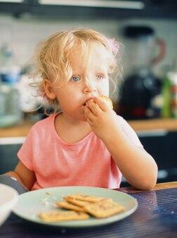 Portrait d'une petite fille aux cheveux blonds ébouriffés prenant son petit déjeuner dans la cuisine