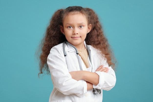 Portrait de petite fille aux cheveux bouclés en blouse médicale debout avec les bras croisés et regardant la caméra sur le fond bleu