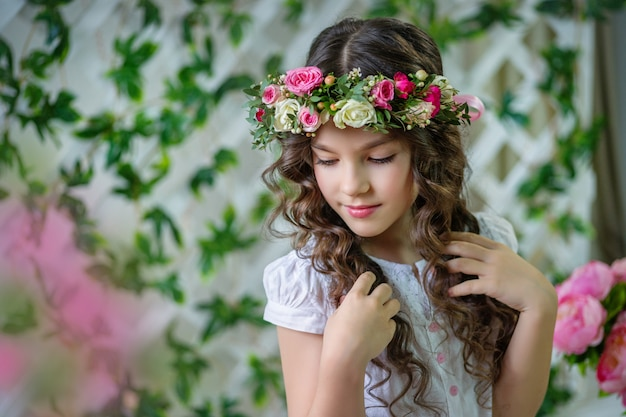 Portrait d'une petite fille aux cheveux longs et une couronne de fleurs fraîches sur la tête. séance photo de printemps.