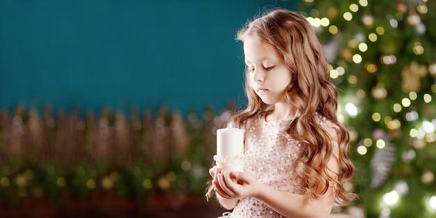 Portrait d'une petite fille aux cheveux longs souriante en robe avec une bougie blanche