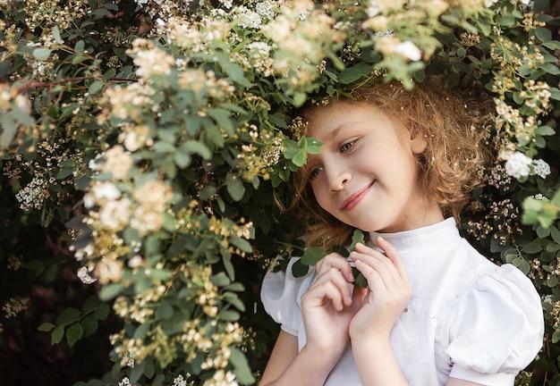 Portrait de petite fille aux longs cheveux blonds, gros plan, buisson en fleurs. concept de printemps.
