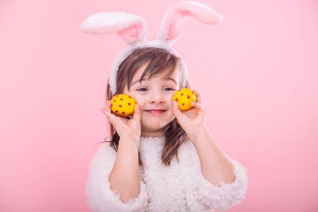 Portrait d'une petite fille aux oreilles de lapin avec des oeufs de pâques