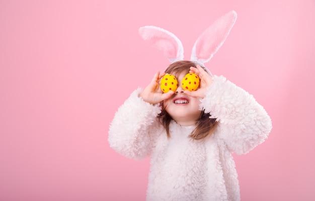 Portrait d'une petite fille aux oreilles de lapin et oeufs de pâques