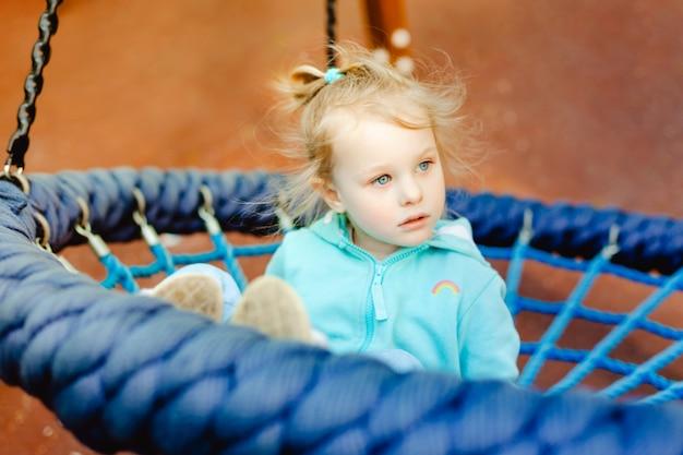 Portrait de petite fille sur balançoire.