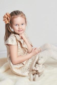 Portrait petite fille belle robe et jouet de poupée