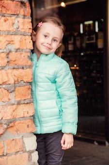 Portrait d'une petite fille blonde caucasienne près d'un mur de briques en regardant la caméra.