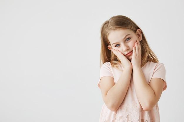 Portrait de petite fille blonde endormie fatiguée aux yeux bleus dans une belle robe rose, tenant le visage avec les mains et à la recherche. copiez l'espace.