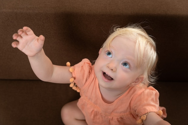 Portrait de petite fille blonde qui a levé la main et demande quelque chose à un adulte.