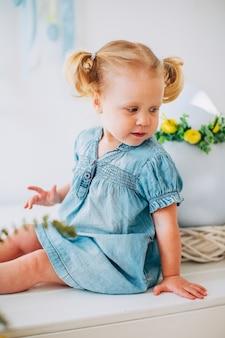 Portrait de petite fille blonde en robe bleue et deux contes de poney dans la salle lumineuse.