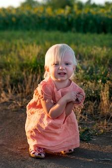 Portrait de petite fille blonde en robe rose à l'extérieur