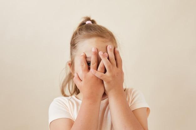 Portrait de petite fille cachant son visage avec les mains, elle joue à cache-cache isolé sur fond blanc