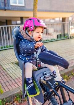 Portrait de petite fille avec un casque de sécurité sur la tête assise dans un siège de vélo prêt à faire une promenade. concept de sécurité et de protection des enfants.