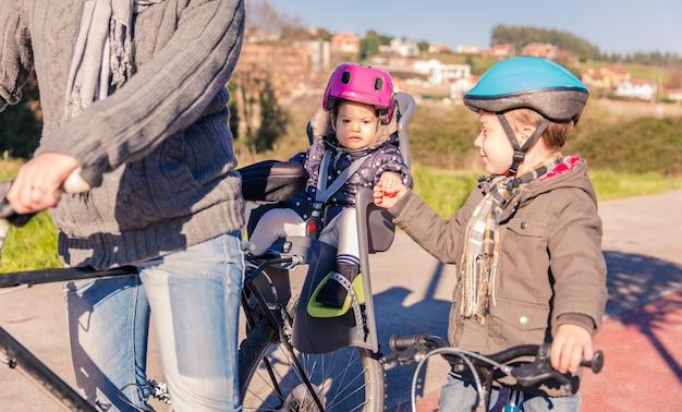 Portrait d'une petite fille avec un casque de sécurité sur la tête assise dans un siège de vélo et serrant la main de son frère. concept de sécurité et de protection des enfants.