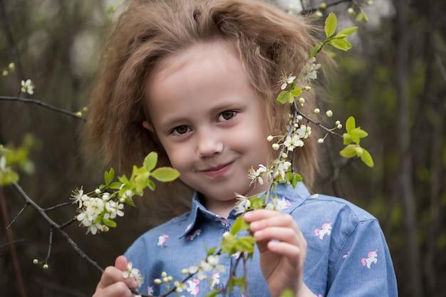 Portrait de petite fille caucasienne de 5 ans dans un parc debout sous un cerisier en fleurs