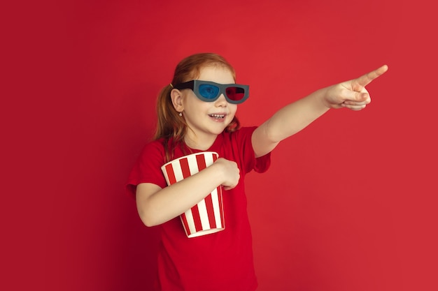 Portrait de petite fille caucasienne isolé sur studio rouge