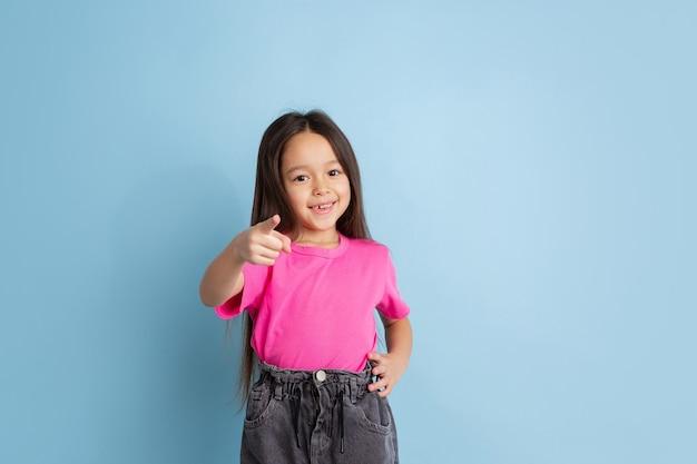 Portrait de petite fille caucasienne sur le mur bleu du studio