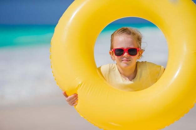 Portrait de petite fille avec cercle de caoutchouc gonflable sur les vacances à la plage