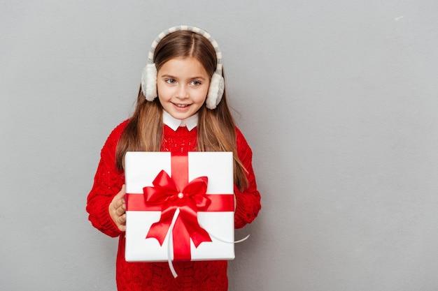 Portrait de petite fille cheerul en pull rouge et cache-oreilles avec boîte-cadeau