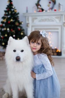 Portrait d'une petite fille avec un chien à l'intérieur du nouvel an