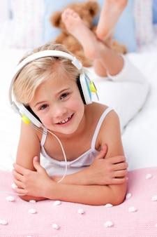 Portrait de petite fille couchée dans son lit en écoutant de la musique