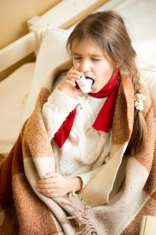 Portrait de petite fille couverte de plaid à l'aide d'un spray pour la gorge