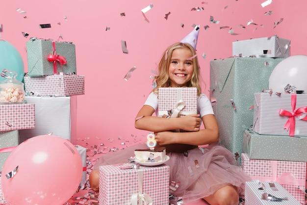 Portrait d'une petite fille dans un chapeau d'anniversaire célébrant