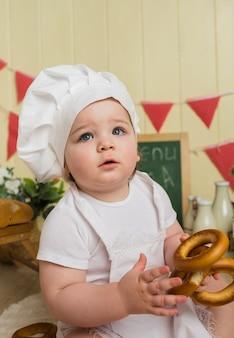 Portrait d'une petite fille dans un chapeau de chef tenant un bagel