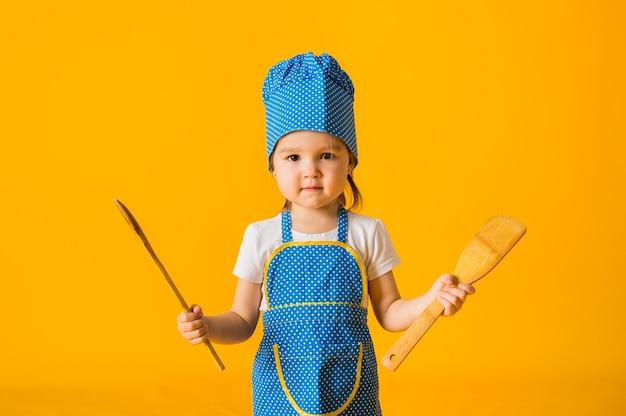 Portrait d'une petite fille dans un costume de cuisinier tenant des cuillères en bois sur une surface jaune avec un espace pour le texte