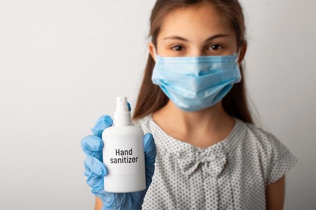 Portrait d'une petite fille dans un masque médical et des gants tenant un désinfectant pour les mains