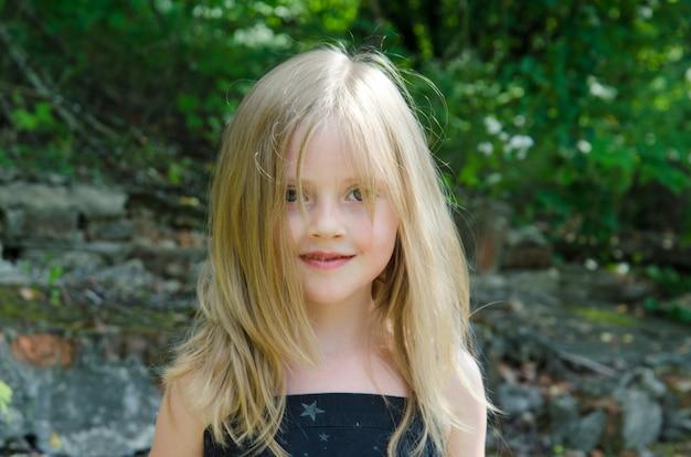 Portrait d'une petite fille dans un pré d'été avec des décorations de fleurs sur le terrain